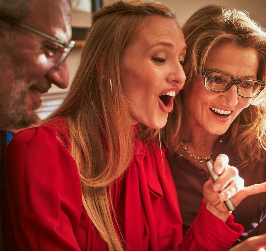 Three joyful people, one holding an IQOS device.