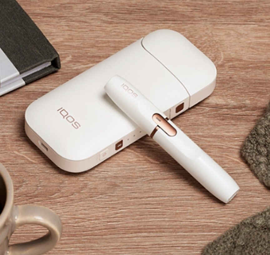 An IQOS 2.4 PLUS on a wooden table.