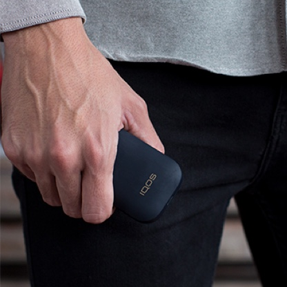 A person holding a white IQOS 2.4 PLUS.